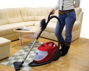 vacuuming hardwood floor with a rug
